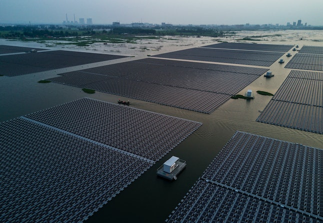 Workers ride in a boat through a large floating solar farm project under construction by the Sungrow Power Supply Company on a lake caused by a collapsed and flooded coal mine on June 13 in Huainan, Anhui province, China.