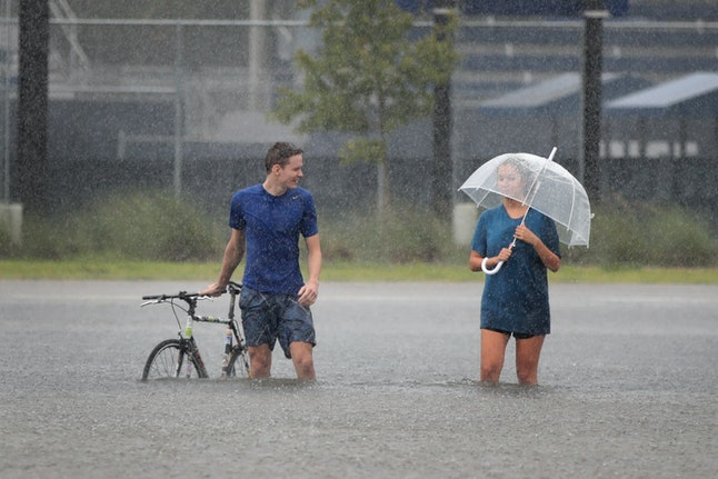Cade Ritter and Mari Zertuche walk through a flooded parking lot on the campus of Rice University.