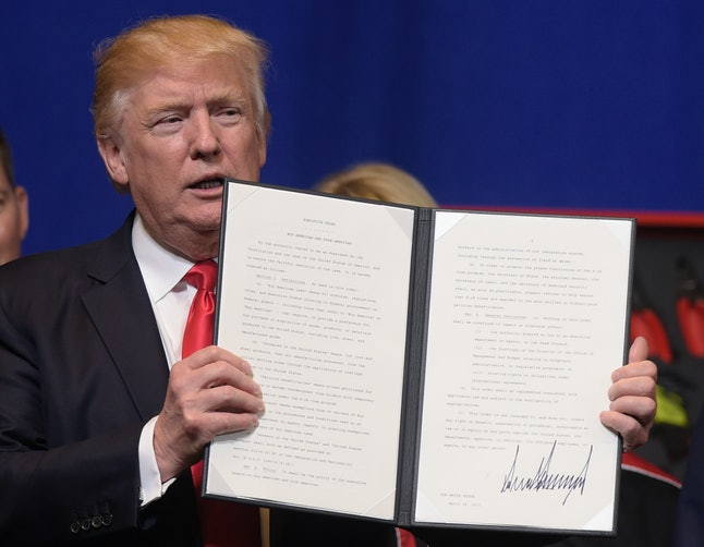 Trump shows off an executive order he signed.