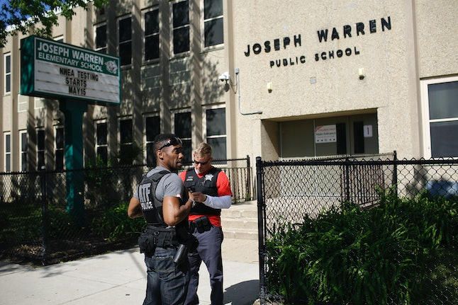 A Bureau of Alcohol, Tobacco, Firearms and Explosives agent and a Chicago Police officer stand outside Warren Elementary School where two girls were shot during a school picnic on June 16.