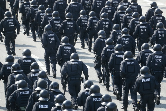 Police officers run down a street that was blocked by demonstrators on the first day of the G20 summit.