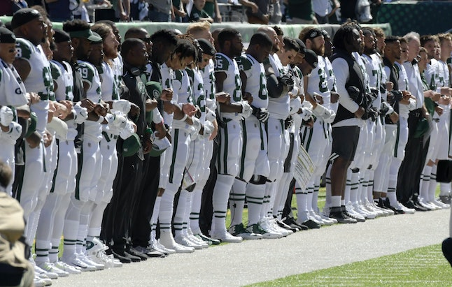 New York Jets link arms during the national anthem before an NFL game against the Jacksonville Jaguars on Sunday in East Rutherford, New Jersey.