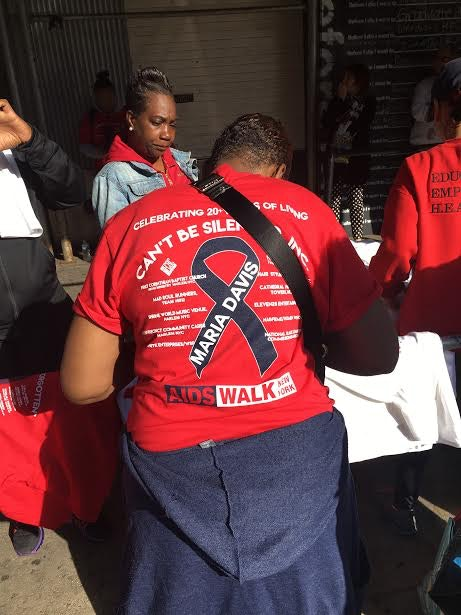 Maria Davis handing out shirts for the 2016 AIDS Walk outside of First Corinthian Baptist Church early Sunday morning.