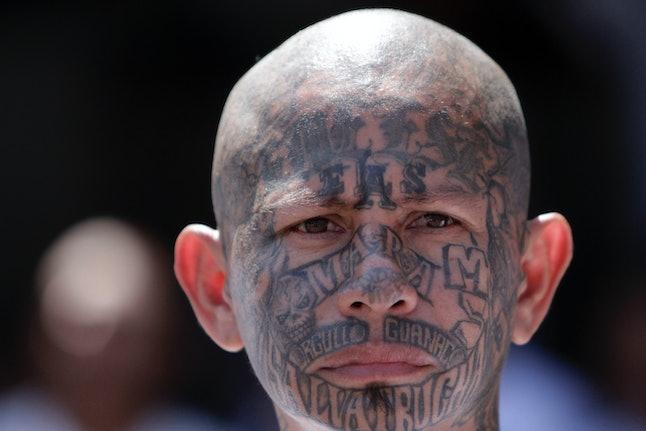 An MS-13 member stands in El Salvador's Ciudad Barrio prison.