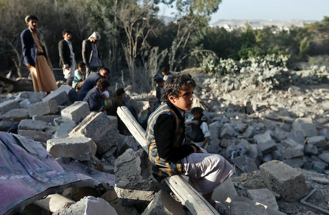 A Yemeni boy sits amidst the rubble of damaged houses following reported Saudi-led coalition air strikes on the outskirts of the Yemeni capital Sanaa on February 1, 2017.