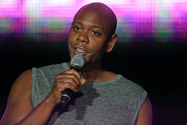 Dave Chappelle performs on stage.