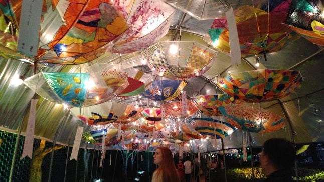 A woman walks through a scene of umbrella lanterns made by elementary and middle school students at the Jinju Namgang Yudeung Lantern Festival in Jinju, South Korea.