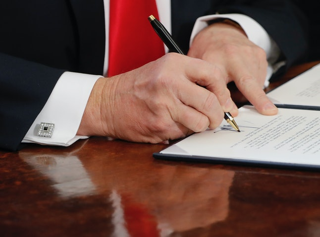 Trump signs an executive order in the Oval Office.