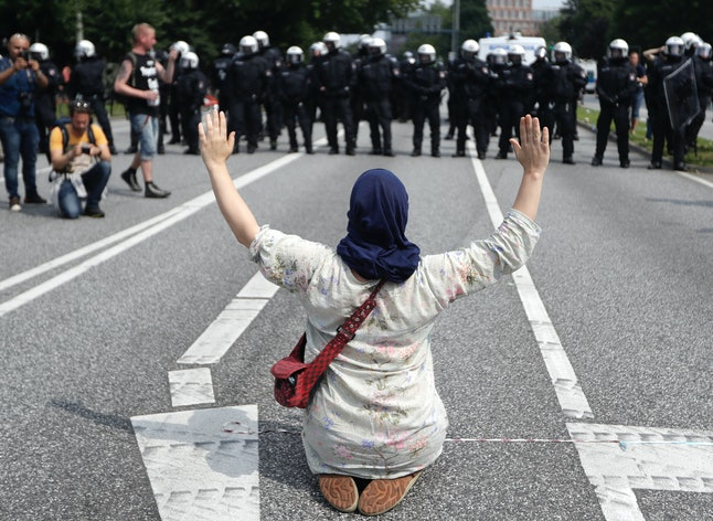 A woman raises her arms as she kneels on a road in front of police officers on July 7.