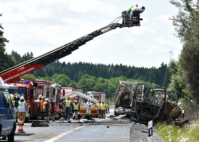 Forensic experts take pictures of the scene where a tour bus burst into flames in Germany on Monday.