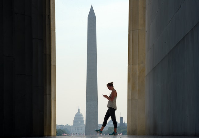 With the Capitol and Washington Monument in the background, a woman visits the Lincoln Memorial in Washington, D.C.