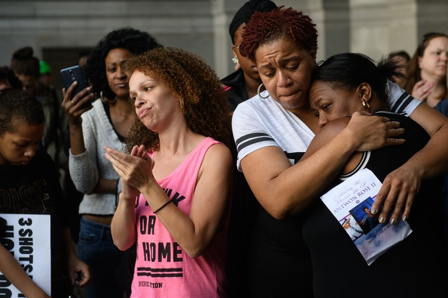 Family members of Antwon Rose Jr. embrace as they listen to speakers during a protest Tuesday in downtown Pittsburgh.