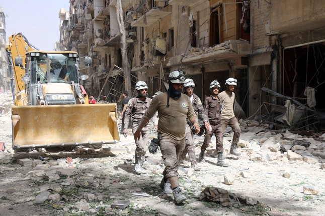 """Local civil defense volunteers named """"White Helmets"""" survey damage after a suspected government airstrike."""