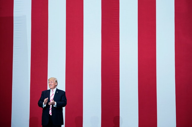 President Donald Trump stands before an oversized American flag at a rally in Alabama.