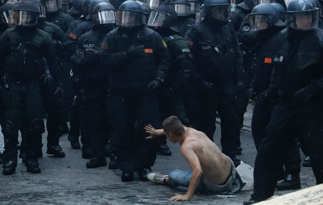 A man, sitting on the ground, gestures as police officers walk toward him during a protest against the G20 summit in Hamburg.