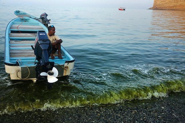 An algae-filled wave washes on the beach in Bandar al-Jissah, Oman.