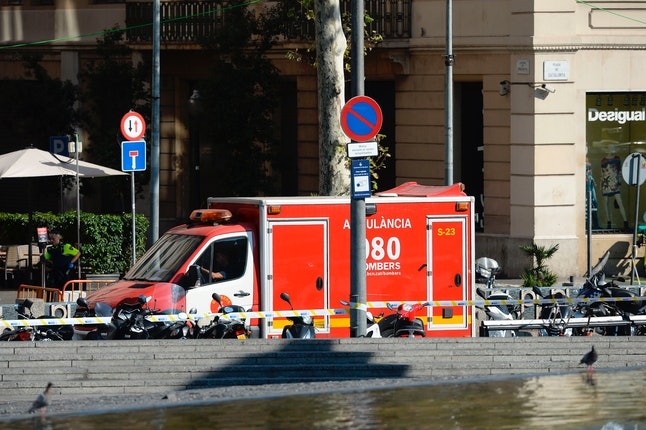 A policeman stands next to an ambulance after a van plowed into the crowd, injuring several people on the Rambla in Barcelona on August 17.