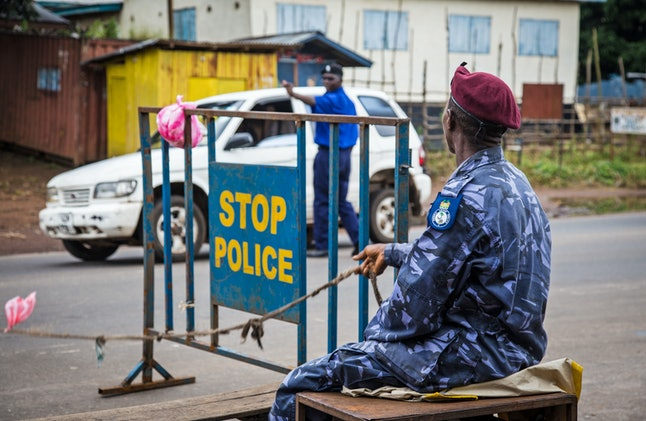 Police guard a roadblock as Sierra Leone government enforces a three day lock down on movement of all people in an attempt to fight the Ebola virus in Freetown, Sierra Leone, Friday, Sept. 19, 2014