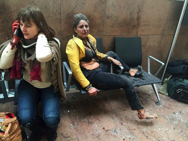 Two women sit stunned at an airport in Brussels after the March 2016 terror bombing that killed at least 32 people.