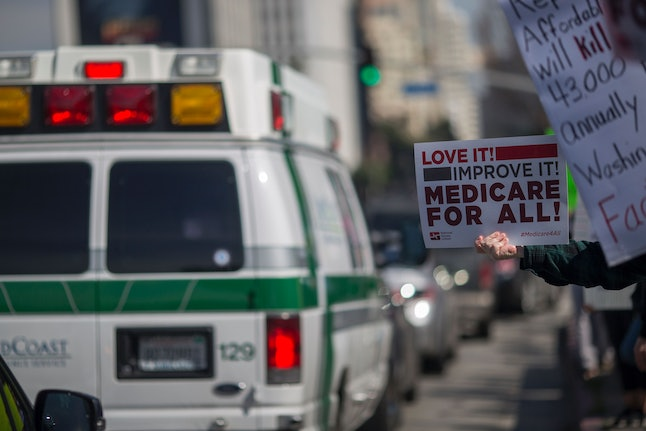 An ambulance passes people protesting Trump administration policies that threaten the Affordable Care Act, Medicare and Medicaid.