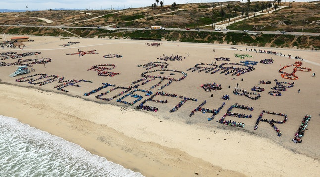 """After cleaning up the beach, students create ocean artwork and spell out """"Come Together For The Ocean,"""" the theme of during the 24th annual Kids Ocean Day beach cleanup at Dockweiler State Beach in Los Angeles, Thursday, May 25, 2017."""