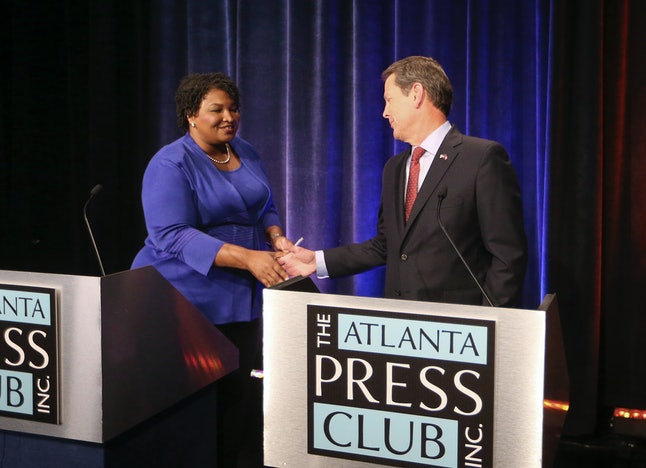 Georgia gubernatorial candidates Democrat Stacey Abrams, left, and Republican Brian Kemp, right, shake hands before a debate that also included Libertarian Ted Metz at Georgia Public Broadcasting in Midtown on Oct. 23 in Atlanta.