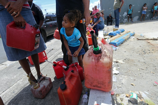 Abi de la Paz de la Cruz, 3, holds a gas can as she waits in line with her family to get fuel from a gas station in San Juan, Puerto Rico.