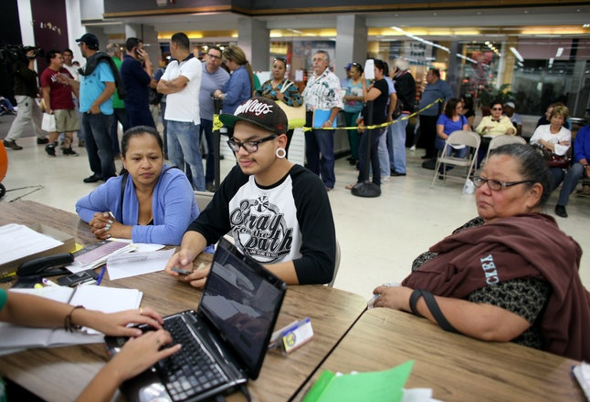 Gexon Orozco sits with his mother, Claudia Gonzalez (L) and grandmother Consuelo Salmeron (R) to get a health care plan under the Affordable Care Act.
