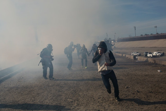 Migrants run from tear gas launched by U.S. agents after a group of migrants got past Mexican police Sunday at the Chaparral crossing in Tijuana, Mexico.