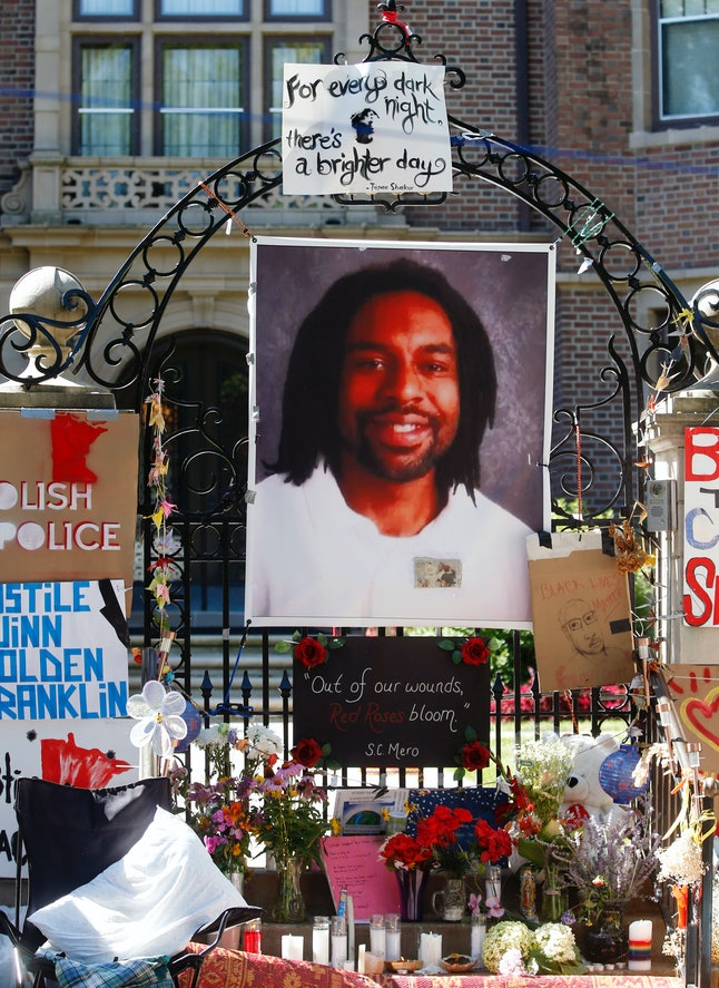 A memorial includes a photo of Philando Castile on the gate to the Minnesota governor's residence.
