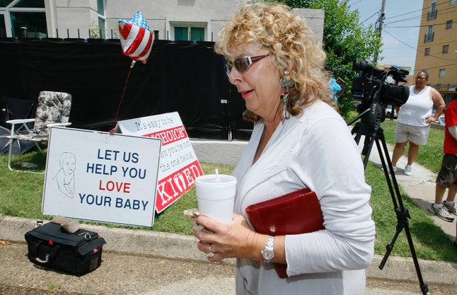 Woman walks past protest signs on way into Mississippi clinic.