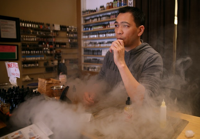 A man who sells vaporizers and their accessories smokes behind the counter.