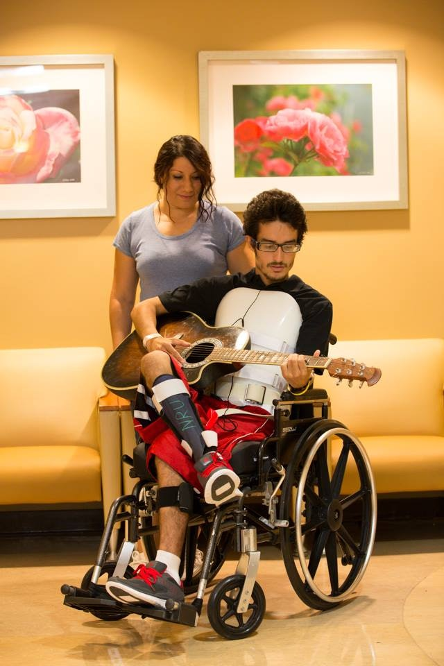 A patient at the Barrow Neurological Institute plays guitar as his mother looks on.