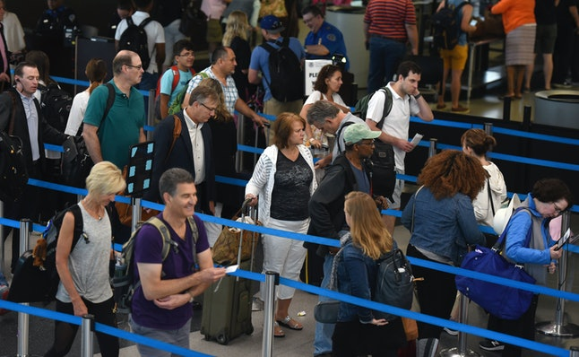 Travelers line up for a security check at O'Hare International Airport in Chicago at the beginning of the holiday weekend Friday, June 30.