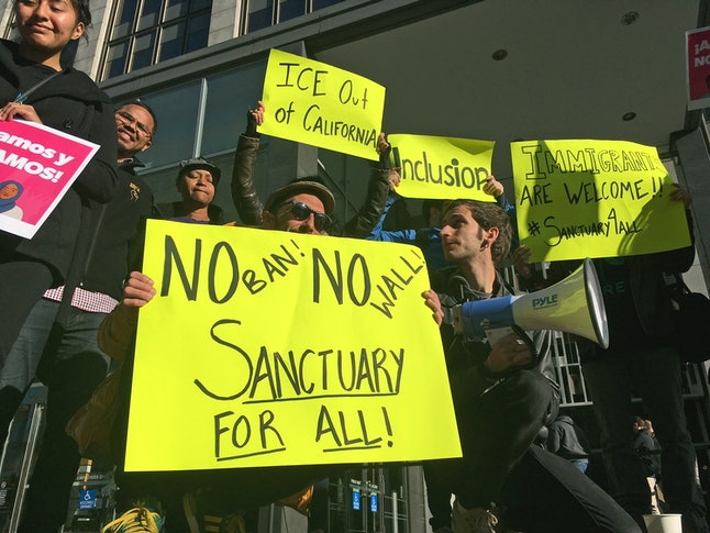 Supporters of sanctuary cities hold up signs in California.