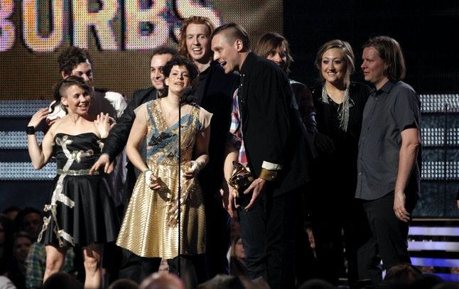 Regine Chassagne, center left, and Win Butler, center right, are joined by fellow band members of Arcade Fire to accept the award for album of the year at the 53rd annual Grammy Awards on Sunday, Feb. 13, 2011, in Los Angeles.
