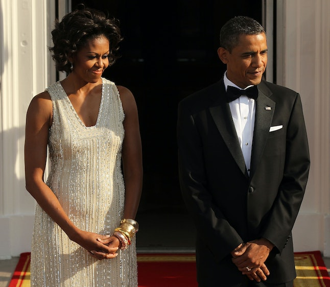 Barack Obama and Michelle Obama wait for the arrival of German Chancellor Angela Merkel before a state dinner in June 2011.