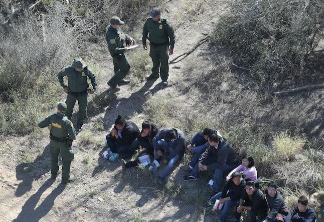 U.S. Border Patrol agents stand alongside immigrants who crossed the U.S.-Mexico border on January 3.