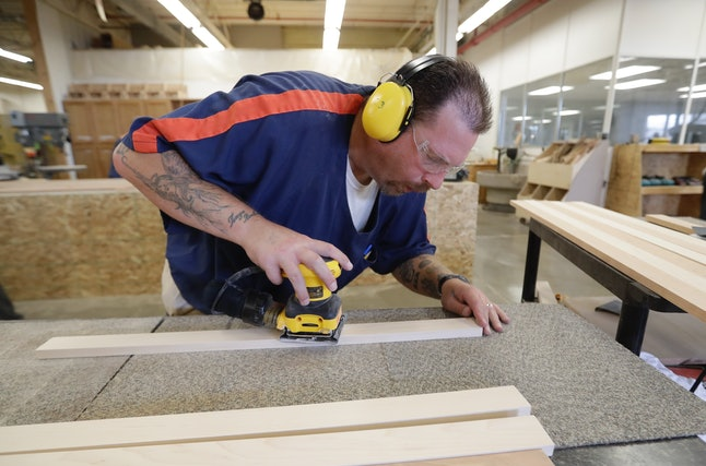 Inmate Bryan Harr sands wood at the Habitat for Humanity Prison Build at the Ionia Correctional Facility.