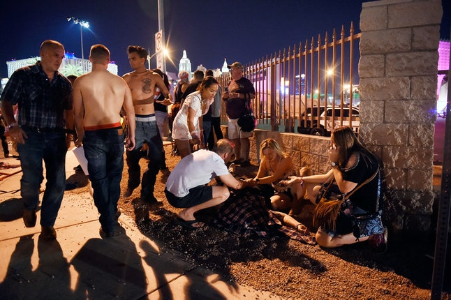 People tend to the wounded outside the Route 91 Harvest festival grounds in Las Vegas.