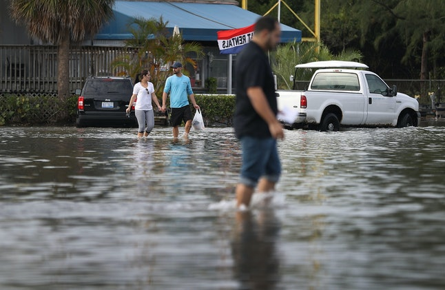 South Florida residents wade through high waters in a North Miami parking lot. Earth scientists say climate change is causing the sea level to rise in coastal areas.