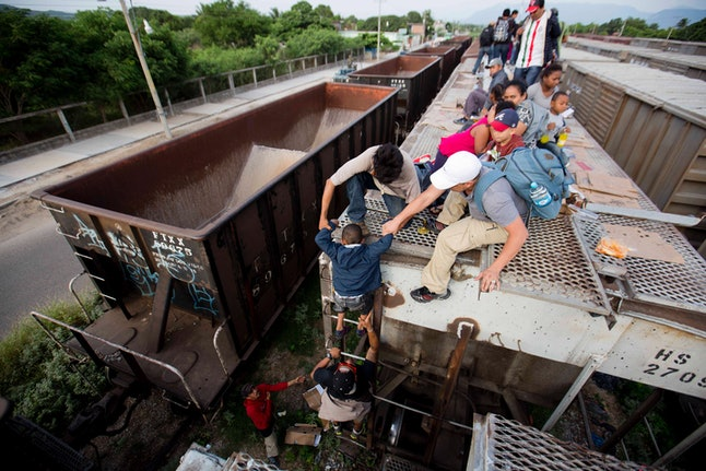 A young boy is is helped down from the top of a freight car, as Central Americans board a northbound freight train in Ixtepec, Mexico, in July 2014.