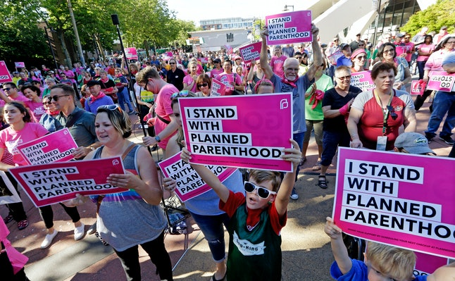 Seattle Storm fans and others cheer at a rally in support of Planned Parenthood before a WNBA basketball game between the Storm and the Chicago Sky on July 18, 2017, in Seattle.
