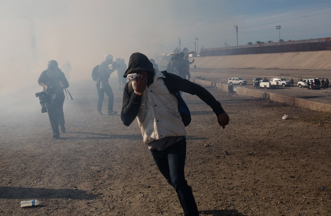 A migrant runs from tear gas launched by U.S. agents near Tijuana, Mexico, on Sunday