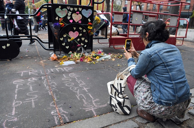 A woman takes a photo at Brooklyn's Adam Yauch Park, where someone spray-painted swastikas on the playground in November.