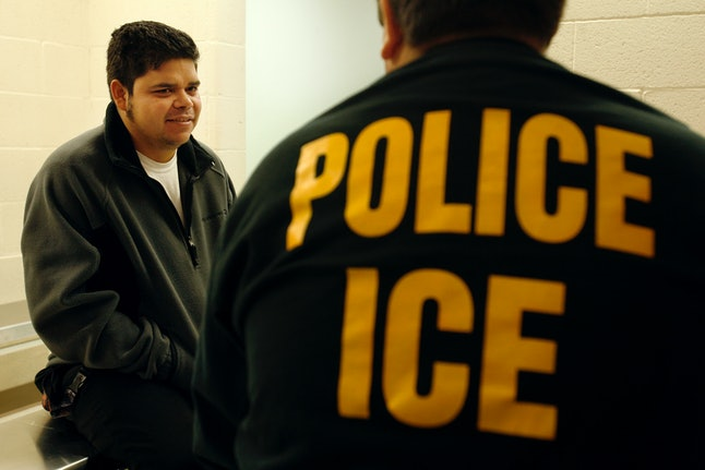 An ICE officer interviews an immigrant from Santa Barbara, California, during 2007 raids that resulted in 338 immigrants being arrested in their homes.