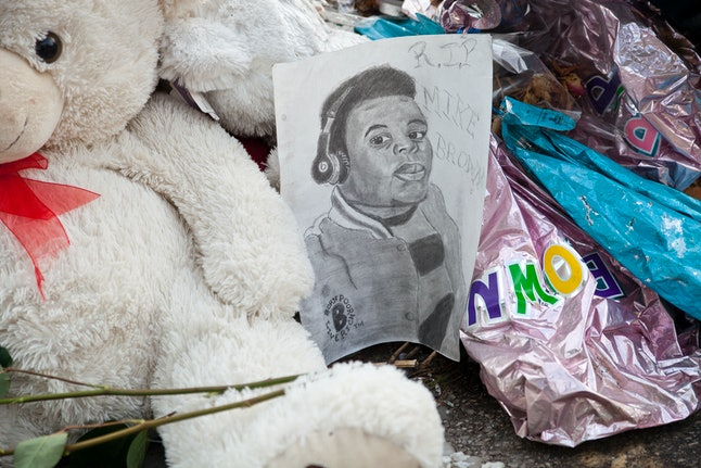 A vigil in Ferguson includes artist's drawing of Michael Brown, an unarmed black teen killed by police in 2014.