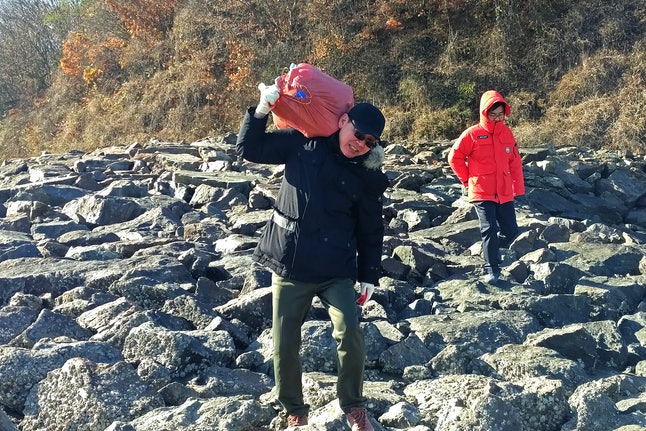 Jung carries a red sack of water bottles — filled with rice, tampons and USB drives — to dump in the Yellow Sea on Nov. 18.