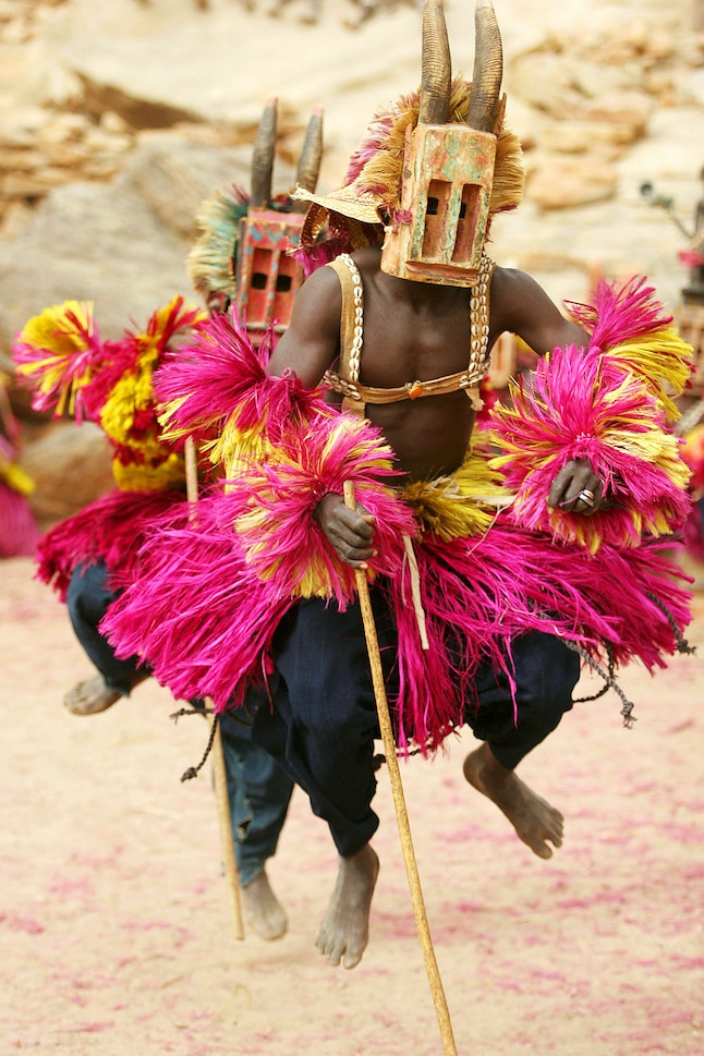 Picture taken on February 9, 2005 shows two Dogon residents wearing traditional outfits and masks performing a dogon dance in a village near the sandstone cliffs of Bandiagara in the center of Mali.