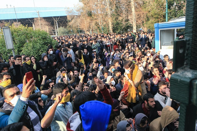 University students attend a protest inside Tehran University while anti-riot Iranian police prevent them to join other protestors, in Tehran, Iran, on Saturday.